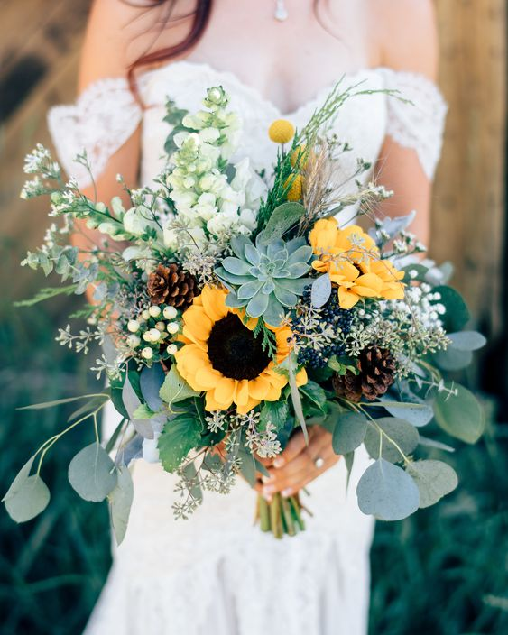 a chic and textural wedding bouquet of white blooms, greenery, sunflowers, succulents and pinecones