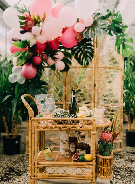 a chic rattan tropical bridal shower cart with lots of refreshing drinks, fruits, blooms and a rattan backdrop with monstera leaves and bright balloons