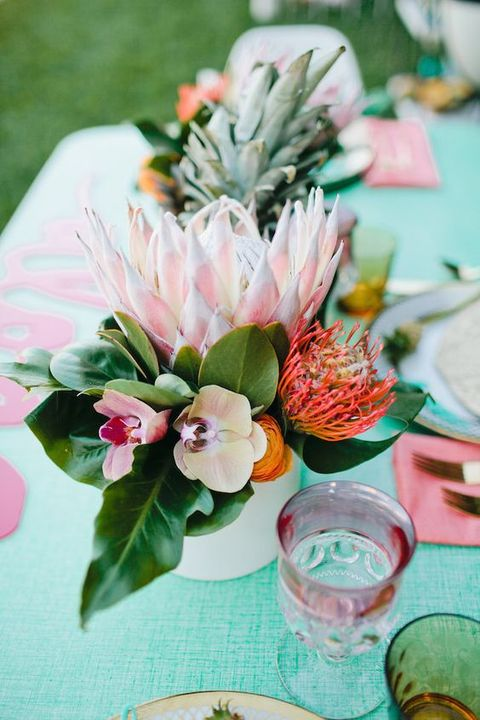 a chic tropical bridal shower centerpiece with orchids and proteas plus greenery