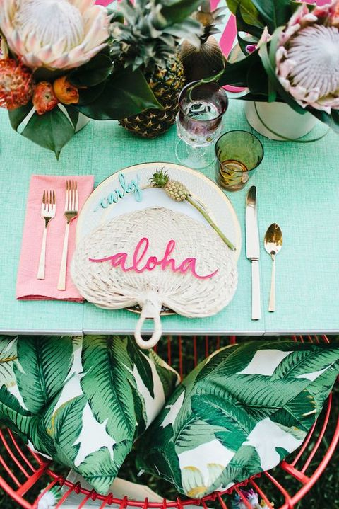a chic tropical bridal shower place setting with a woven fan, a grene tablecloth, king proteas and a pineapple plus banana print pillows
