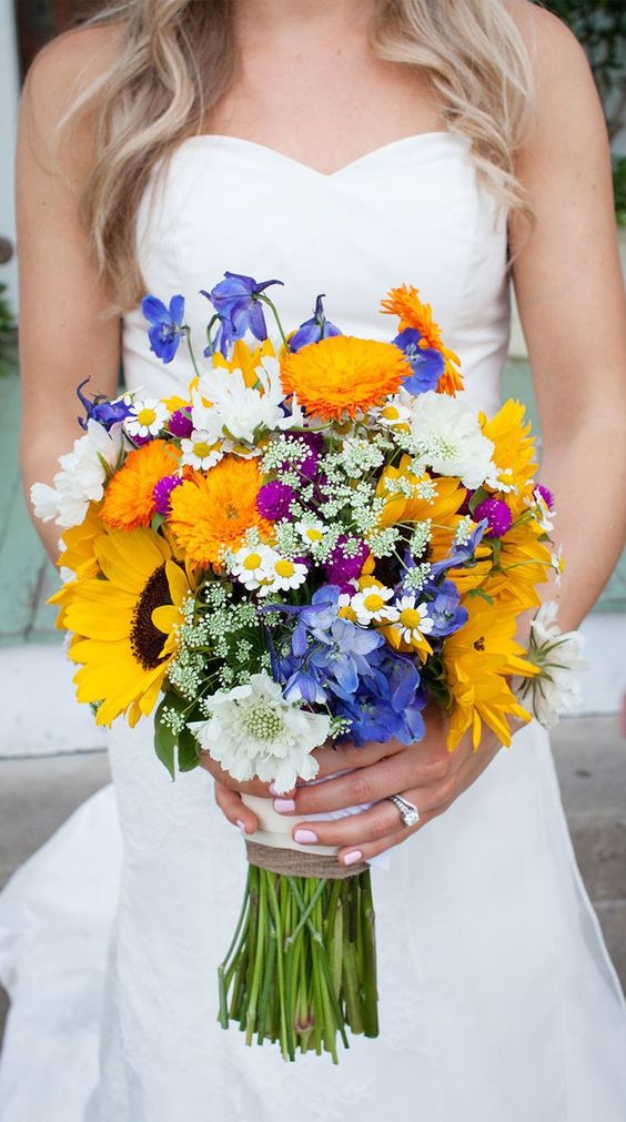 a colorful summer wedding bouquet of white, blue and marigold blooms and sunflowers for a rustic bride
