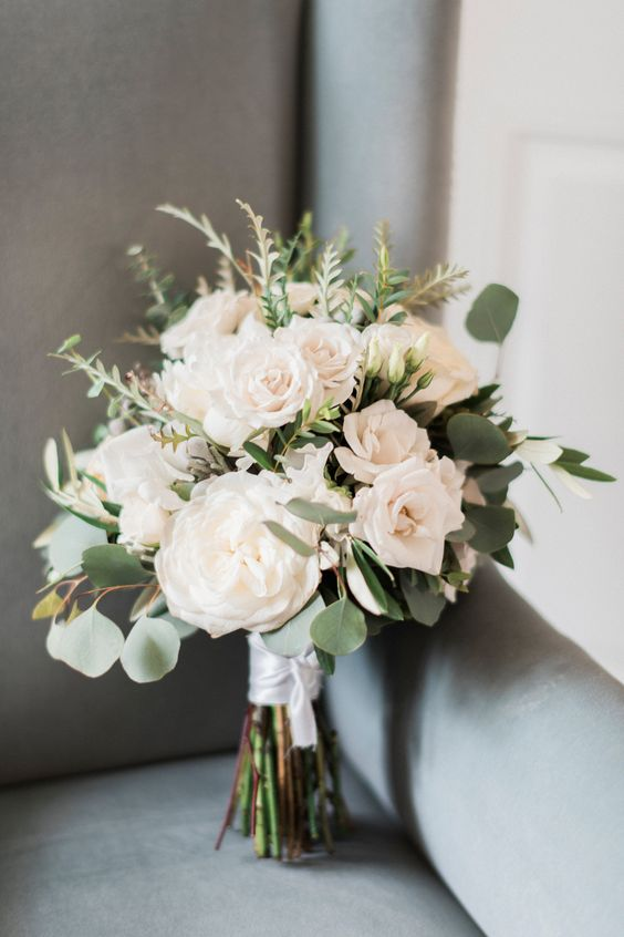 a cool white wedding bouquet of peonies and roses, some herbs and greneery plus a white ribbon