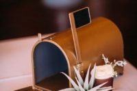 a copper mailbox with a flag and an air plant plus some blooms for a modern wedding