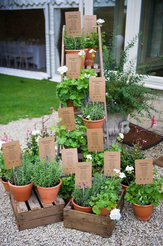 a creative wedding seating chart made of a ladder and crates and potted greenery plus cardboard with tables