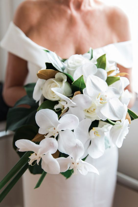 a creative white orchid and rose wedding bouquet with foliage and magnolia leaves