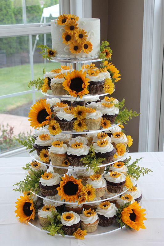 a cupcake stand decorated with fresh sunflowers and cupcakes and the cake themselves decorated with sugar ones, too