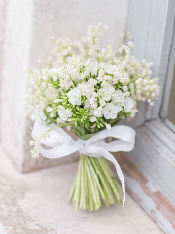 a cute white wedding bouquet of lily of the valley and some other blooms plus a bow for a casual bride