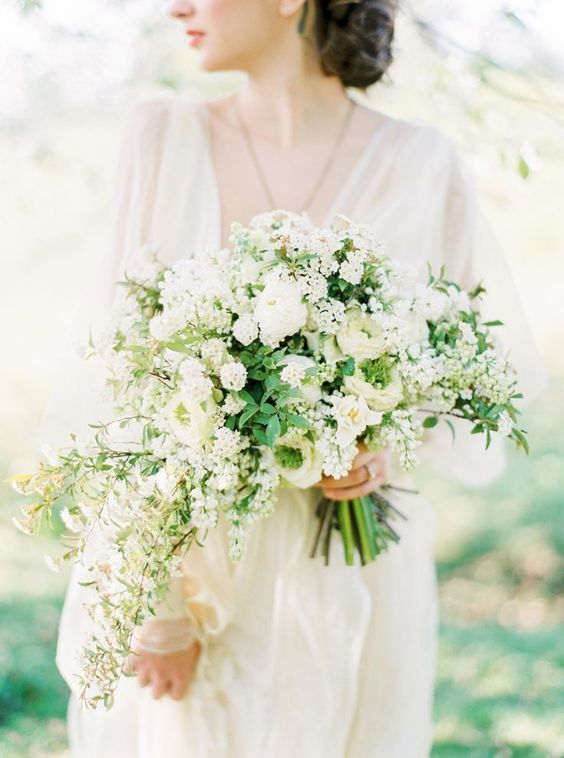 a dimensional white wedding bouquet with a cascading part and greenery for a chic and romantic look