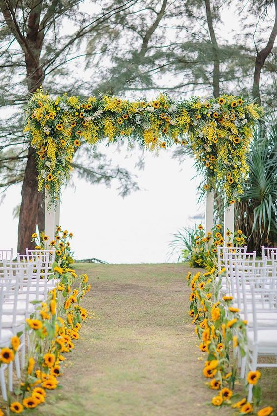 a fall wedding ceremony space done with textural greenery, sunflowers and sunflowers lining up the aisle