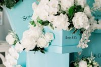 a fun bridal shower decor idea with tiffany blue boxes, white roses, greenery and little vases with blooms