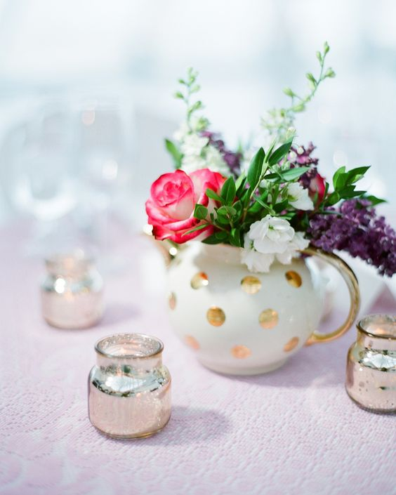 a gold polka dot teapot with pink, purple and white blooms and silver candle holders