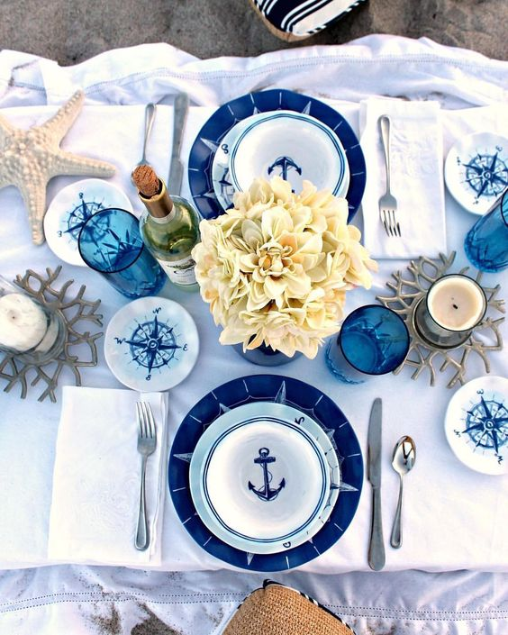 a gorgeous nautical shower tablescape with navy and blue plates, neutral blooms, compasses, starfish and blue glasses