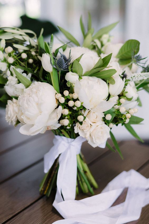 a gorgeous wedding bouquet with white peonies, berries, thistles and greenery plus a white ribbon