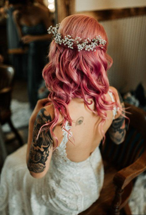 a lace sheath wedding dress with an open back, pink wavy half updo with waves and a halo with baby's breath for a wow look