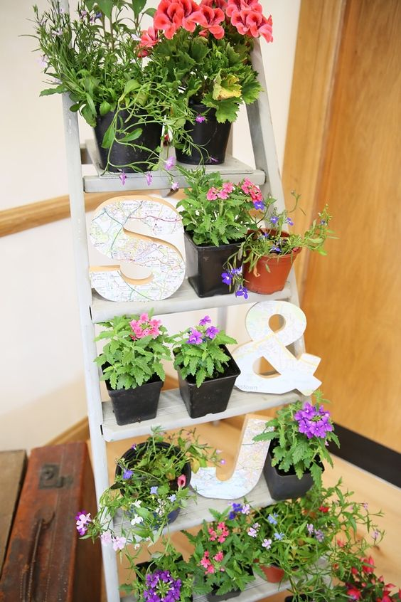 a ladder with potted greenery and bright flowers plus letters is a cool idea to decorate your space in a bold way