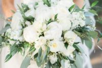 a large and lush wedding bouquet with white peonies and other blooms and much greenery, which is cascading