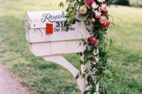 a large vintage mailbox on a stand decorated with greenery and fresh blooms is classics to meet your guests