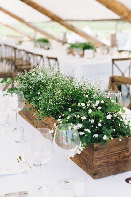 a long rustic planter with several types of white flowers and greenery will refresh your wedding reception