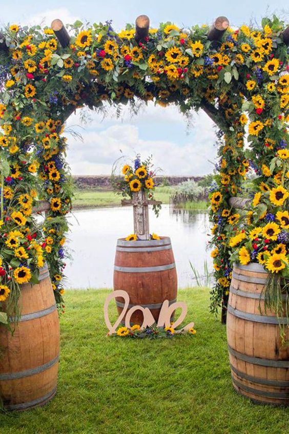 a lush and bold wedding arch done with sunflowers, blue and red blooms and much greenery