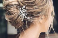 a messy wavy French twist updo with a messy top, a messy twisted chignon and locks down plus a rhinstone hairpiece
