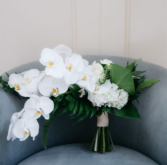 a modern tropical wedding bouquet of white orchids and tropical leaves and ferns is a statement idea