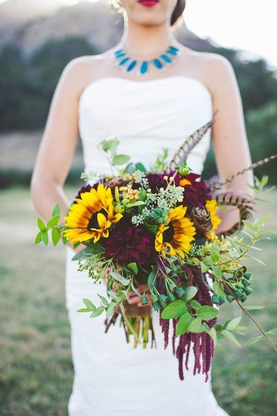 a moody fall wedding bouquet done with greenery, deep purple blooms and sunflowers for a statement