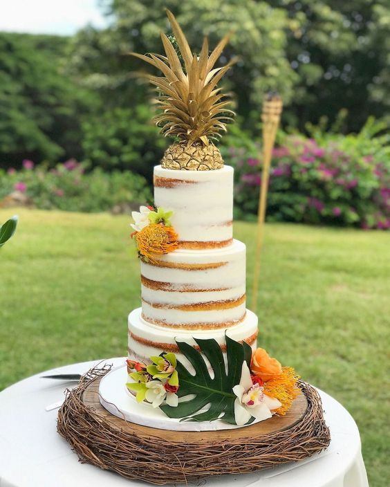 a naked tropical bridal shower cake decorated with a piece of pineapple, some bright tropical blooms and a monstera leaf