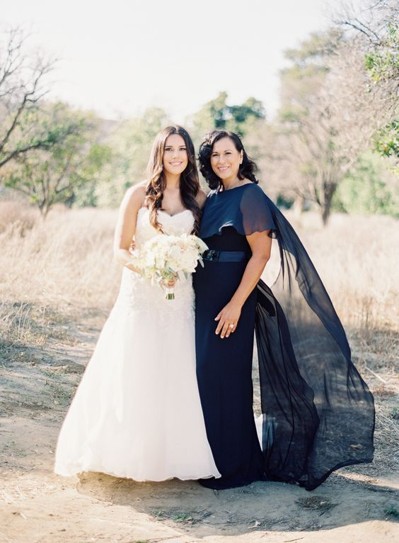 a navy maxi dress with a fitting silhouette, a sash and a sheer shawl on top are an amazing outfit for a formal wedding