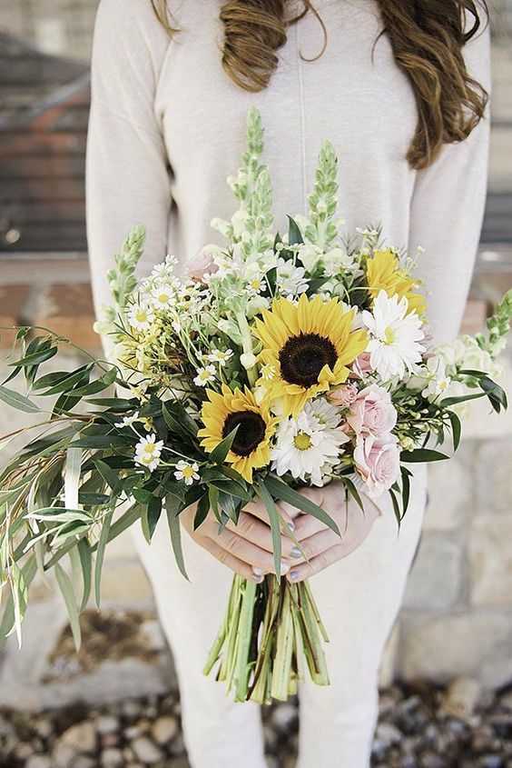 a pale spring wedding bouquet of pink roses, white blooms, sunflowers and lots of greenery