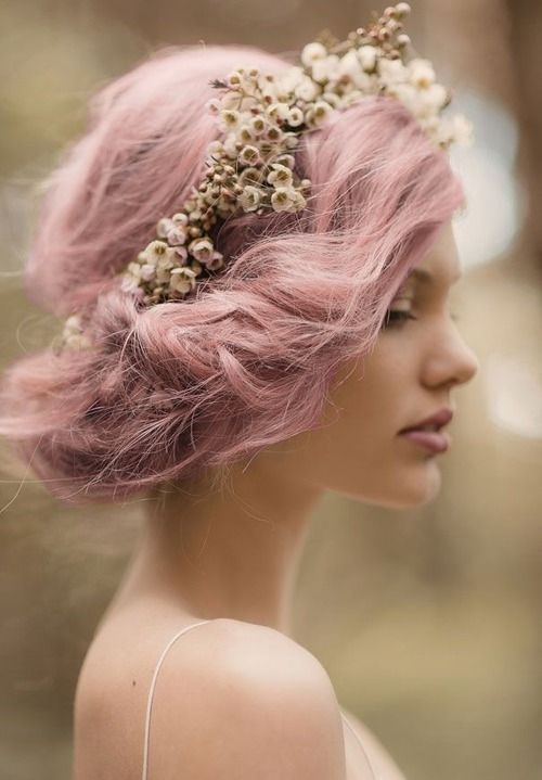a pink twisted wedding side updo with a bump and a floral crown for an airy and romantic spring bridal look
