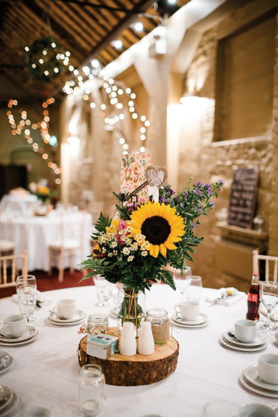 a quirky rustic wedding centerpiece of a wood slice, some jars with petals, a sunflower arrangement and some burlap