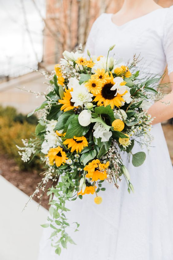a romantic spring wedding bouquet of white blooms, sunflowers and willow pussy plus greenery