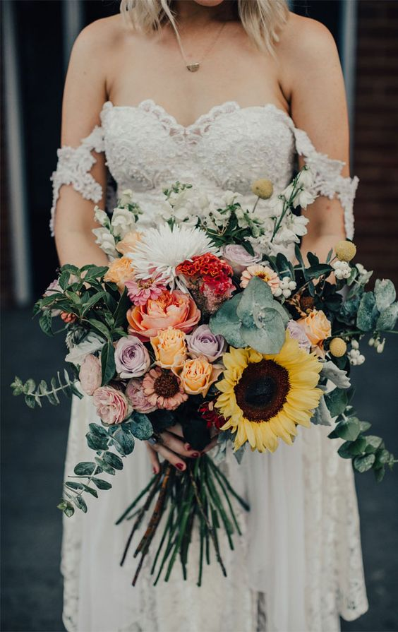 a romantic textural wedding bouquet of sunflowers, pastel blooms and red and white ones plus greenery