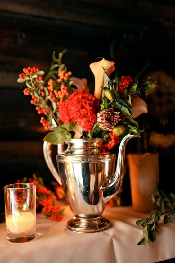 a silver teapot with bright coral red and peachy blooms and berries for a colorful statement