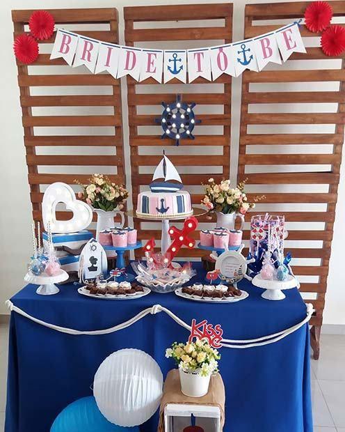 a simple and cute nautical bridal shower dessert table with a banner, some nautical decor, an anchor marquee light and tasty desserts