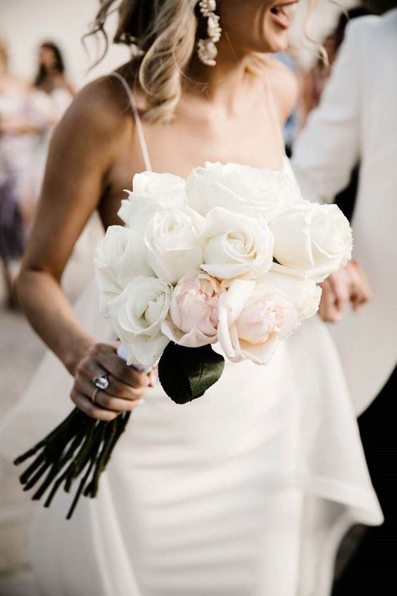 a simple and elegant white and blush wedding bouquet of roses with a unique shape and leaves left