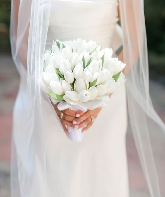a simple and minimal white tulip wedding bouquet with a white silk wrap is a timeless idea for every bride