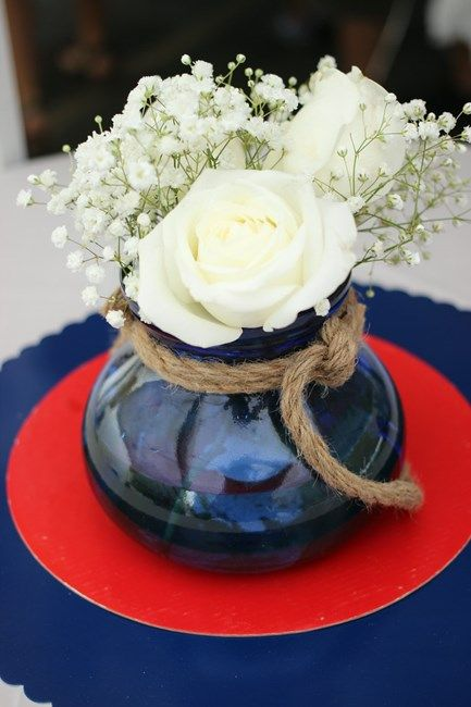 a simple and stylish centerpiece with a red and blue charger, a blue vase with rope and white roses and baby's breath