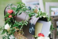 a simple metal mailbox with greenery and bright blooms, with a chalkboard tag and lots of letter