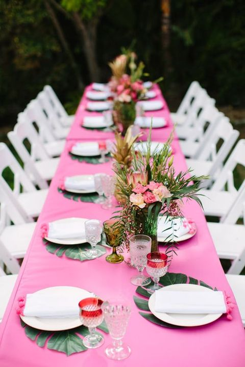 a simple tropical shower tablescape with a pink tablecloth, bright floral arrangements and tropical leaf placemats