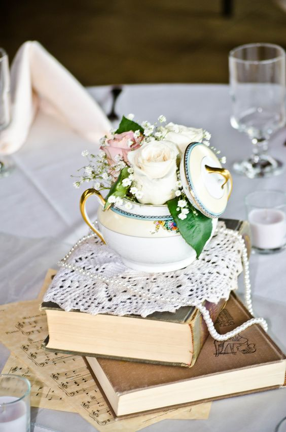 a stack of books, notes, a doily, a teapot, a strand of pearls and pink and white roses and baby's breath