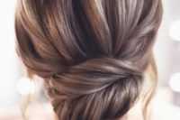 a stylish and chic French twist updo with a voluminous top and a pretty twisted chingon plus locks