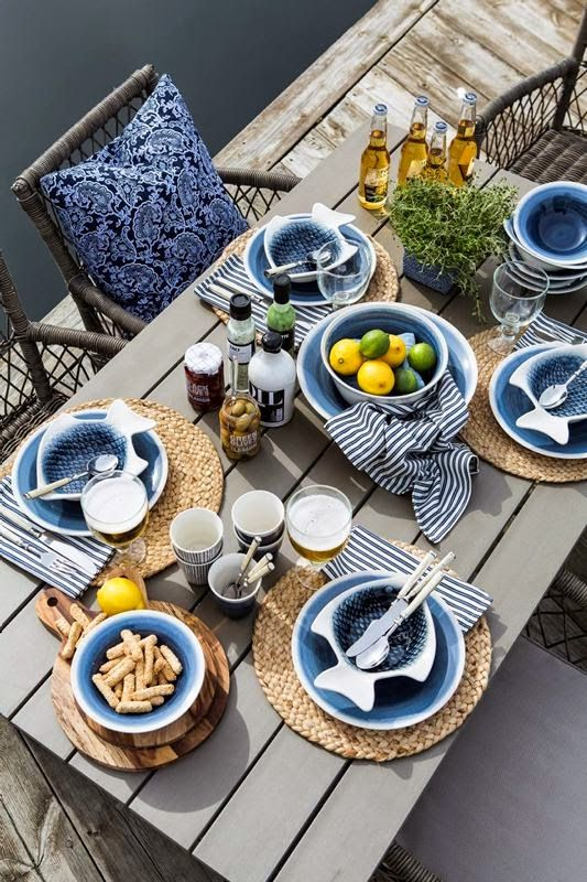 a stylish and simple nautical bridal shower setting with an uncovered table, wicker chargers, blue and fish plates plus a citrus centerpiece