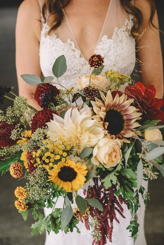 a stylish fall wedding bouquet of sunflowers, burgundy and peachy blooms and much textural greenery