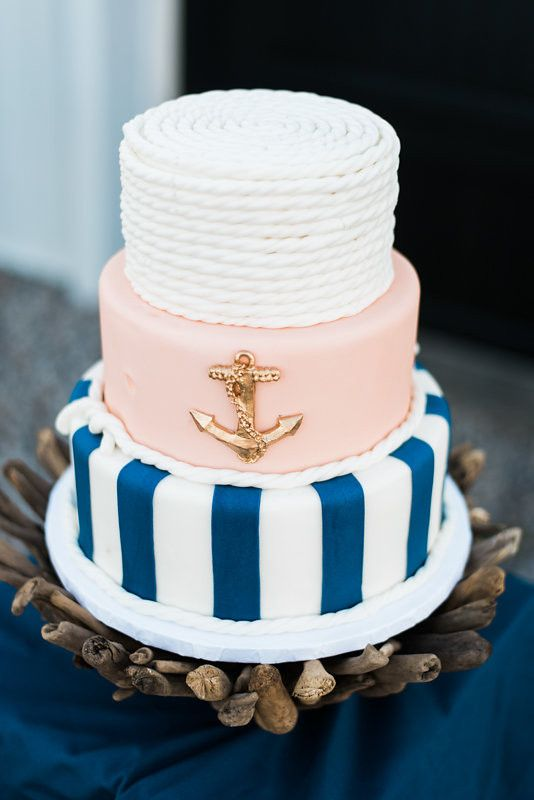 a stylish nautical bridal shower cake with stripes, a pink tier wiht an anchor and a white rope top tier