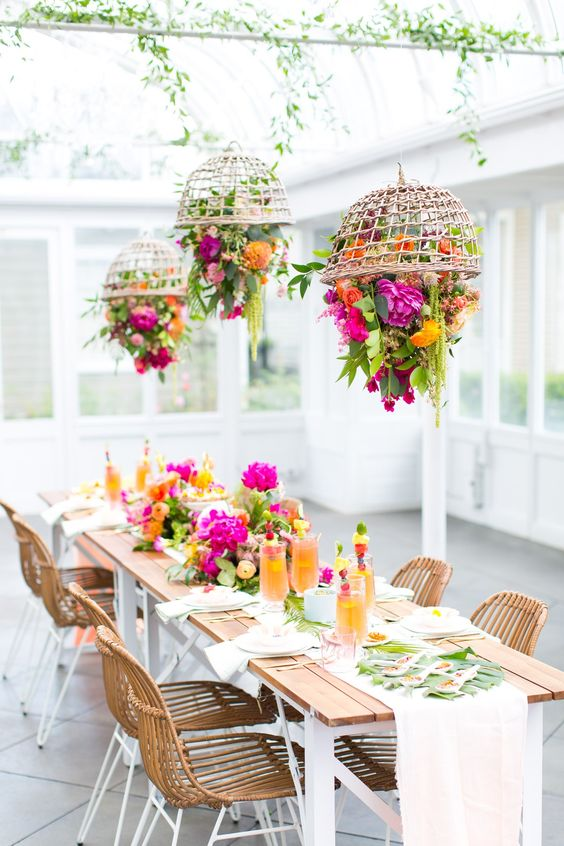 a super colorful bridal shower table setting with bright florals hanging in baskets over the table, floral arrangements on the table and tropical leaves