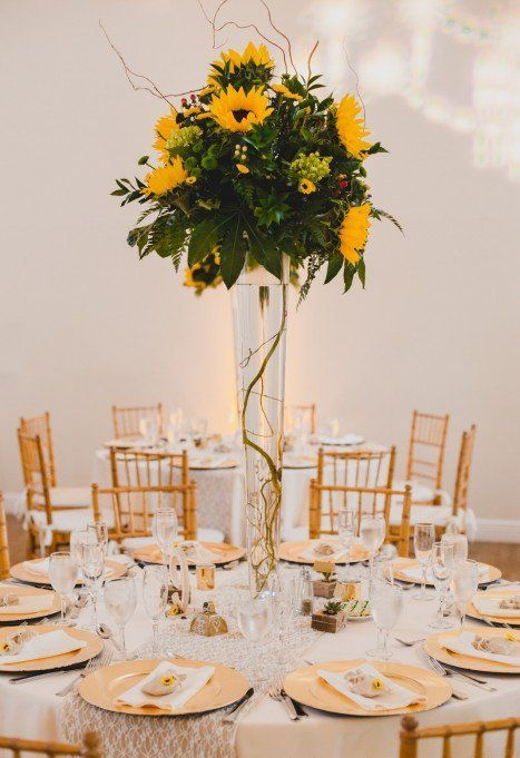 a tall wedding centerpiece of much textural greenery and some sunflowers and twigs over them