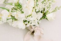 a textural and dimensional white wedding bouquet with some greenery and blush ribbons