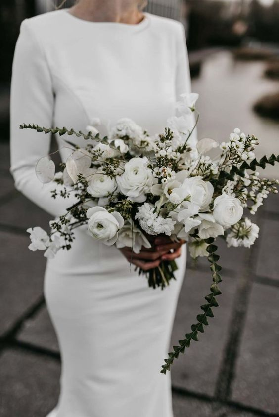 a textural white wedding bouquet of ranunculus, lunaria, little blooms and greenery cascading and not only