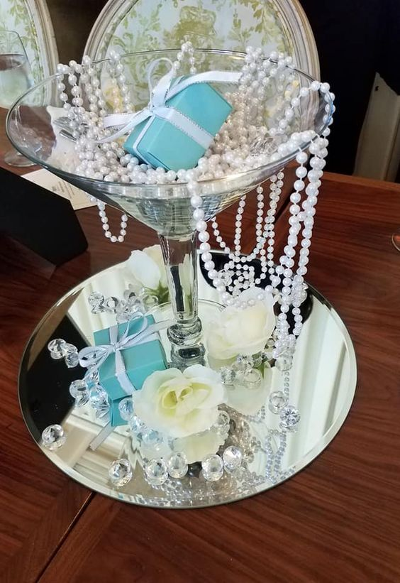 a themed centerpiece of a mirror, a large glass, pearls, roses, rhinestones and tiffany blue gifts